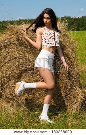 playful woman standing on haystack in summer