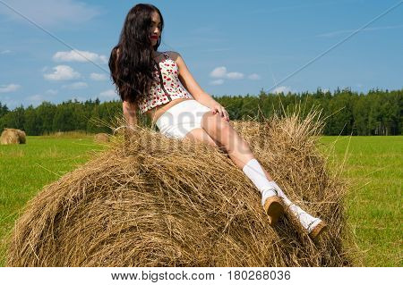 luxurious brunette sitting on haystack in summer