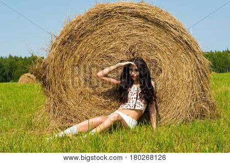 young fashion woman lying on grass on haystack