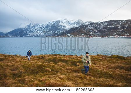 Two photographers are walking on the hill of Lofoten islands winter time