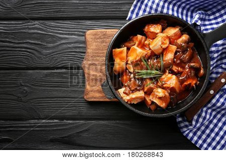 Frying pan with chicken cacciatore on kitchen table