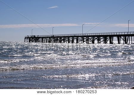 Summer sunlight sparkling over the sea and jetty Semaphore South Australia beach blue water and horizon