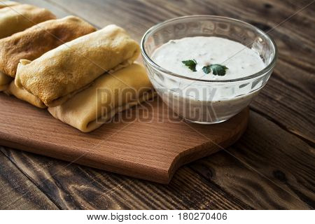crepes with stuffing and white sauce and tomato on wood