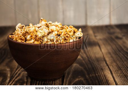 caramel popcorn in clay bowl on wooden background