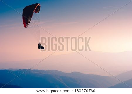 Paraglide silhouette over the misty mountain valley.