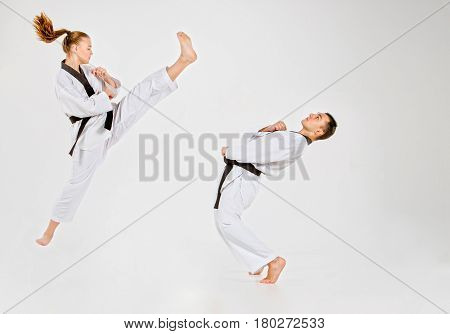 The karate girl and boy in white kimono and black belt training karate over gray background.