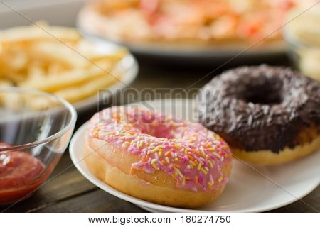 Unhealthy Concept. Unhealthy Food: Burger, Sauce, Potatoes, Donuts, Pizza.