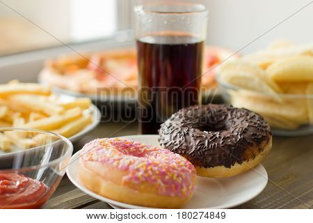 Unhealthy Concept. Unhealthy Food: Burger, Sauce, Potatoes, Donuts, Pizza, Drink.