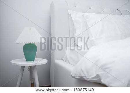 Bedside Table With Green Lamp Near White Clean And Modern Bedroom With Empty Wall