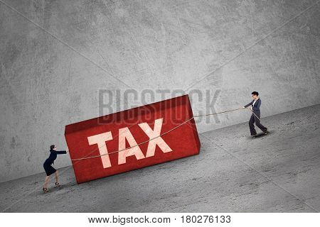 Picture of two businesswomen pulling a boulder with a Tax word. Concept of Tax