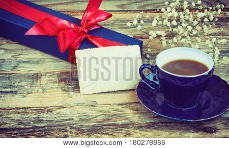 Blue cup of coffee gift box with red ribbon blank paper tag on an old wooden table holiday background retro toned