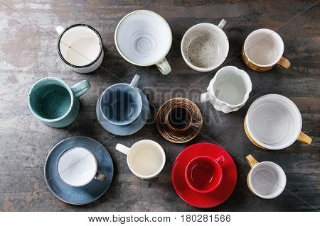 Empty colorful modern ceramic plates and bowls collection. Various of dishware over dark metal background. Top view