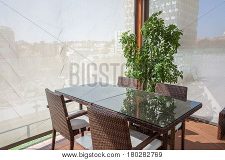 Concept of restaurant interior. Room on the open area with view on city. Ideal place for meetings, negotiations, romantic dinners, lunches, breakfasts, coffee breaks. Wicker furniture made of bamboo