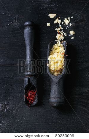 Yellow saffron salt and saffron spice in wooden spoons over black burnt wood background. Top view with space