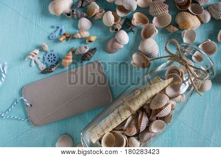 Summer background on wood with message in bottle and tag for text.Marine concept.