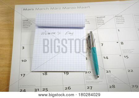 A desk top with notebook pen and calendar. Women's day concept.