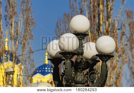 On a bright springy sunny day the white balls of a street lamp shine against the background of the golden and blue domes of the city cathedral.