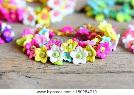 Beautiful children bracelet on vintage wooden table. Bracelet made of colourful plastic flowers, leaves and beads. Floral accessories for a little girl. Closeup