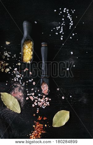 Variety of different colorful salt yellow saffron, pink, white sea in wooden spoons with black, chili, allspice pepper and bay leaves over black burnt wood background. Top view