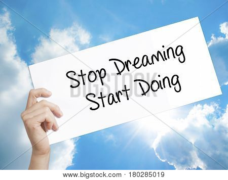Man Hand Holding Paper With Text Stop Dreaming Start Doing  . Sign On White Paper. Isolated On Sky B