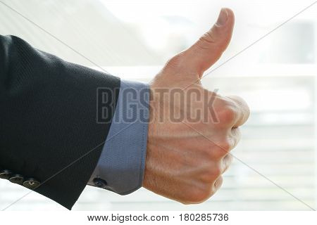 businessman shows thumps up sign for his approval - backhand