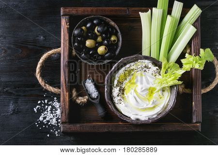Fresh celery with yogurt and olive oil dip in ceramic bowl, served with sea salt and black, green olives on wood tray over black wooden burnt background. Top view with space. Healthy snack