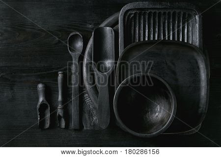 Black burnt wooden empty kitchenware cutting board, plates, scoop and spoon over black wood background. Flat lay with space
