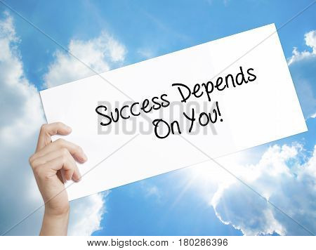 Man Hand Holding Paper With Text Success Depends On You! . Sign On White Paper. Isolated On Sky Back