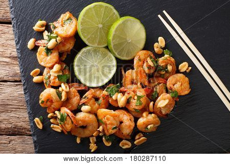 Sauteed Shrimp With Peanuts, Lime And Greens Closeup On The Table. Horizontal Top View
