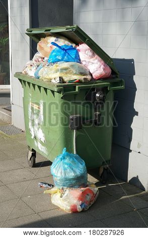 wheeled trash can container overflowing with garbage bags
