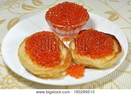 Pancakes with red caviar on a white plate. Russian cuisine