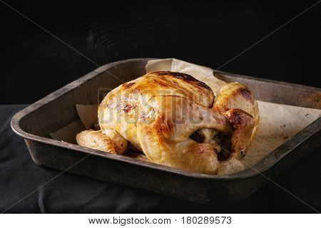 Grilled baked whole organic chicken on backing paper in old oven tray over black burnt wooden background. Top view with space.