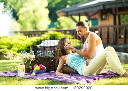 Couple in park on picnic. Young enamoured couple on rest in park. Couple having a picnic in the park on a sunny day.
