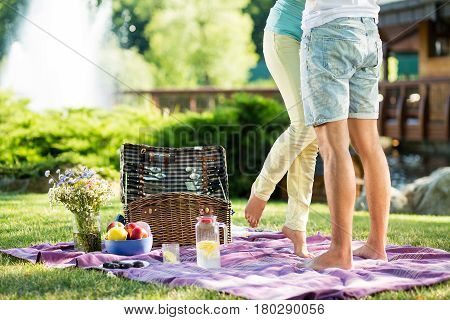 Couple in park on picnic. happy barefoot couple on picnic, girl standing on tiptoe try to kiss husband.