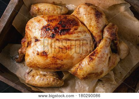 Grilled baked whole organic chicken on backing paper in old oven tray over black burnt wooden background. Top view, close up