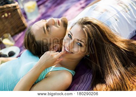 Couple in park on picnic. Beautiful Young Couple Having Picnic in Countryside. Happy Family. Couple having a picnic in the park on a sunny day.