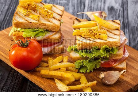 Club Sandwich With Tomato, Lettuce, Bacon, Ham And French Fries