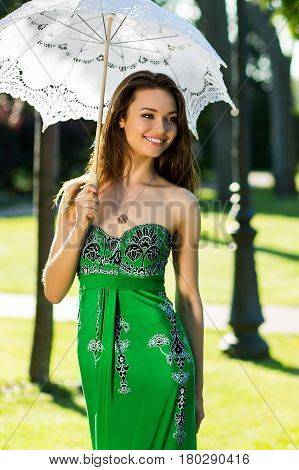 young girl in a green dress walking in the park with white umbrella. smiling beauty woman walks at noon with white umbrella. model walks with umbrella in garden.