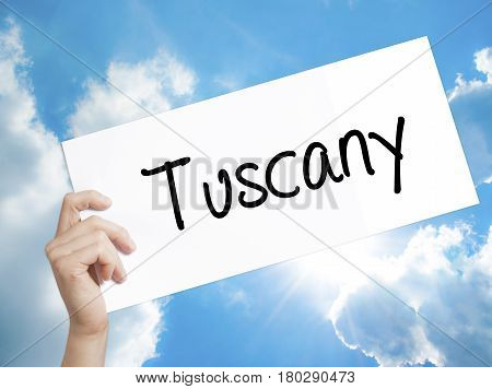 Man Hand Holding Paper With Text Tuscany . Sign On White Paper. Isolated On Sky Background.