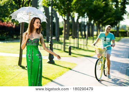 beautifull girl having fun with boyfriend in park. boy follows girlfriend on bicycle in nature. girl looks for her boyfriend.
