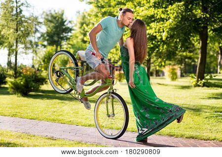 Wonderful kiss of couple on park background. Extreme kiss on bike. Extreme kiss in air. Guy on green bike kisses girl.