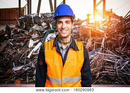 Smiling worker wearing a high-visibility vest in a junkyard
