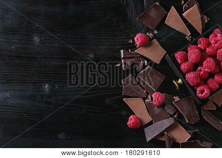 Dark and milk chopping chocolate and chips shavings chopping chocolate with fresh raspberries in black wood box over black burnt wooden background. Top view with space. Chocolate dessert concept