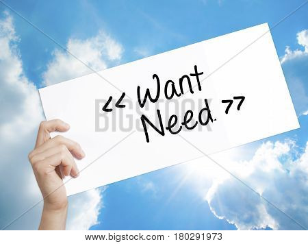 Man Hand Holding Paper With Text Want - Need . Sign On White Paper. Isolated On Sky Background.