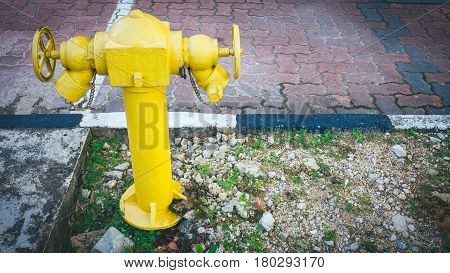 Yellow fire hydrant on street. Typical yellow fire hydrant asian on street. Yellow fire Hydrant vintage style.