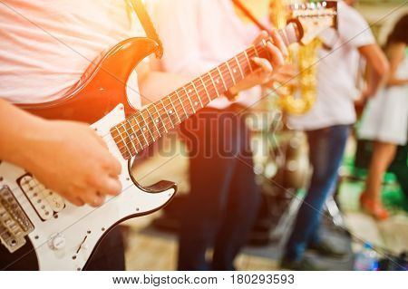 Man Playing On Electric Guitar Against Band.
