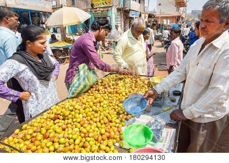 BADAMI, INDIA - FEB 8, 2017: Customers buying fresh fruits at marketplace of traditional indian street market on February 8, 2017. Population of Karnataka state is 62000000 people