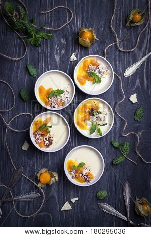 Homemade dessert panna cotta with mango sauce, physalis, mint and chocolate on a wooden background. Top view