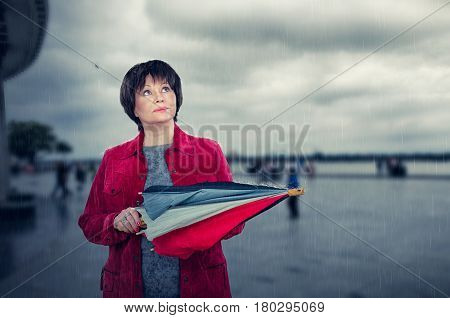 Aged Woman Stands Under Sudden Rain