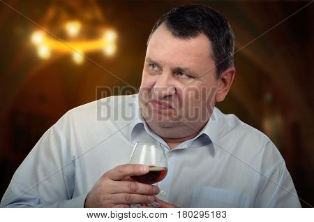 Chubby face annoyed mature man holds glass of brandy by hand. He looks at right side. He wears light blue long sleeve shirt. Close up shot on blurred indoors background